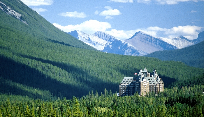 fairmont banff springs surrounded by forest and mountains