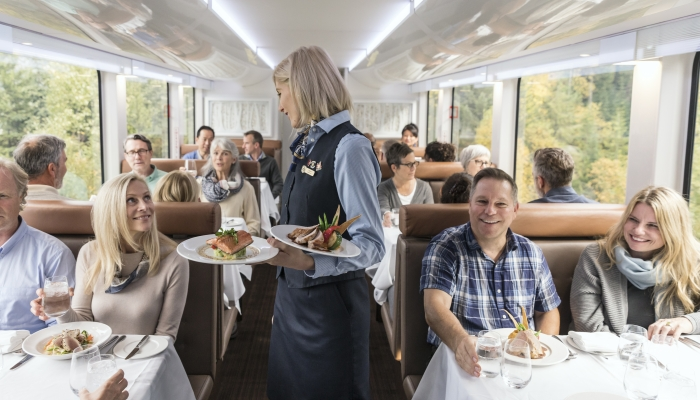host onboard rocky mountaineer serves salmon and ribs to guests in goldleaf service