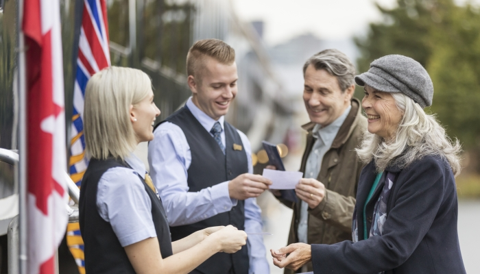 guests show tickets to hosts before boarding the rocky mountaineer train