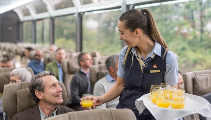 rocky mountaineer host hands out orange juice onboard the train in gold leaf service