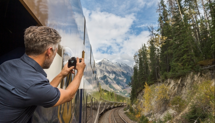 man snaps a photo of mountain range while leaning out of outdoor viewing platform on the journey through the clouds route on the way to Jasper