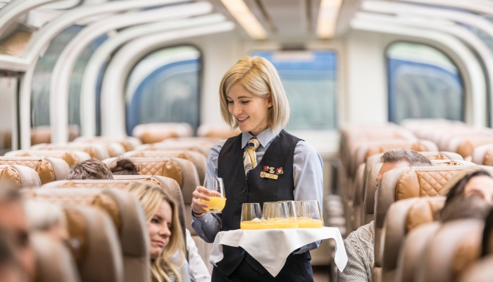 rocky moutaineer host hands out mimosas onboard the train in goldleaf service