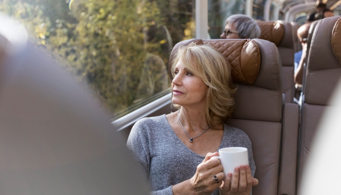 woman holds coffee mug and gazes out window onboard the rocky mountaineer