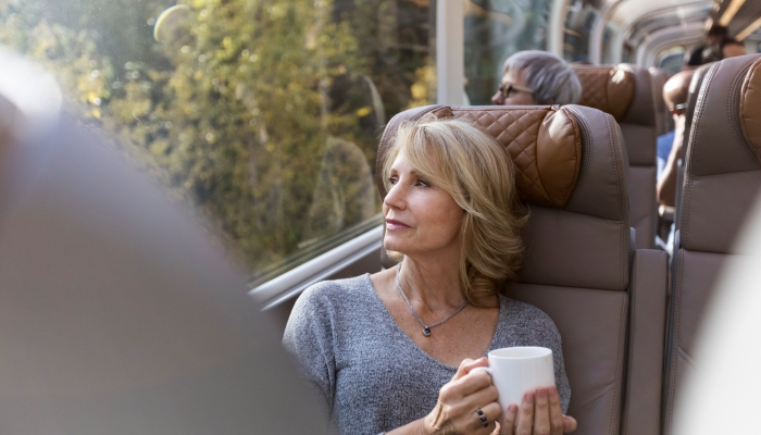 woman looks out the window while seated in goldleaf onboard the rocky mountaineer train